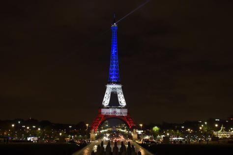 A photo taken on November 16, 2015 in Paris shows the Eiffel Tower illuminated with the colors of the French flag in tribute to the victims of the November 13, 2015 Paris terror attacks. AFP PHOTO / ALAIN JOCARD        (Photo credit should read ALAIN JOCARD/AFP/Getty Images)
